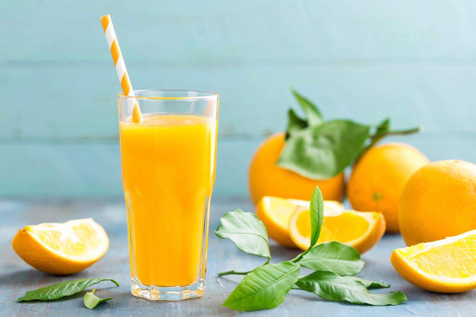 frischpresster Orangensaft im Glas, frische Orangen im Hintergrund auf Holz, vitamin drink